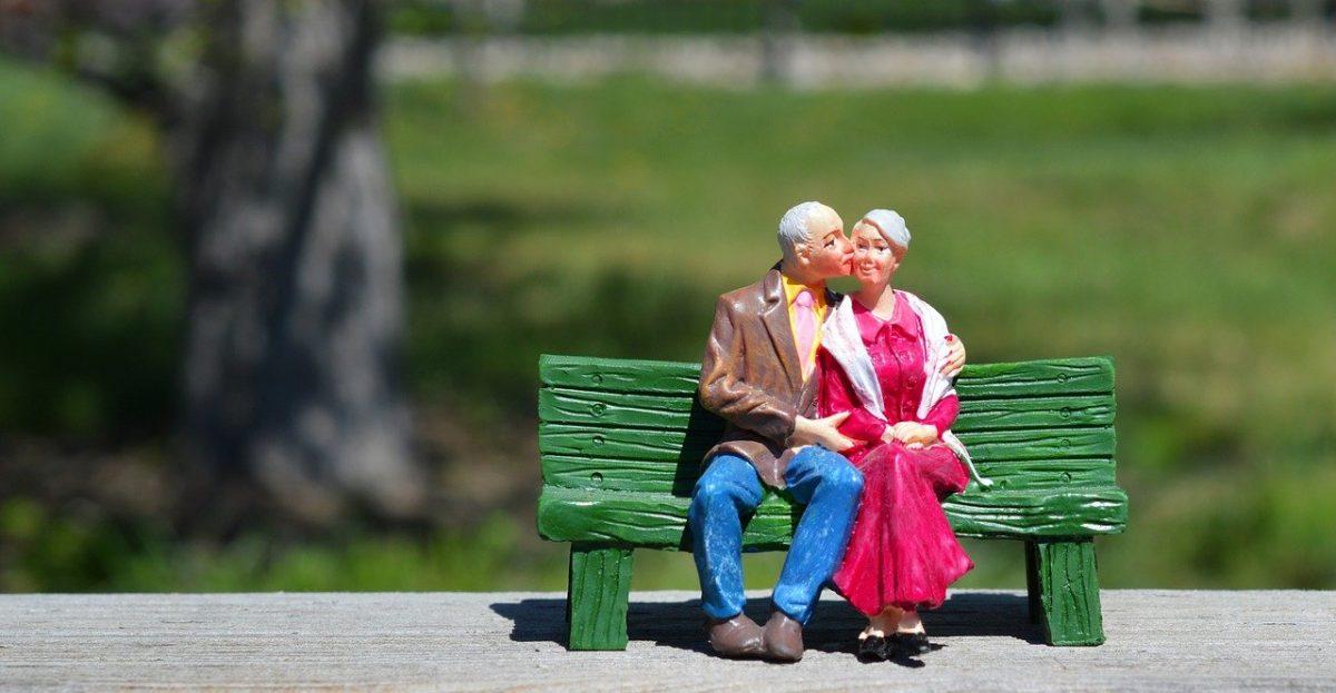Casal de idosos apaixonados sentados no banco da praça