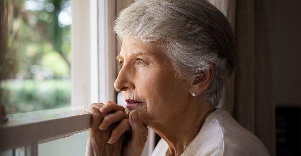 Idosa olhando na janela com depressão