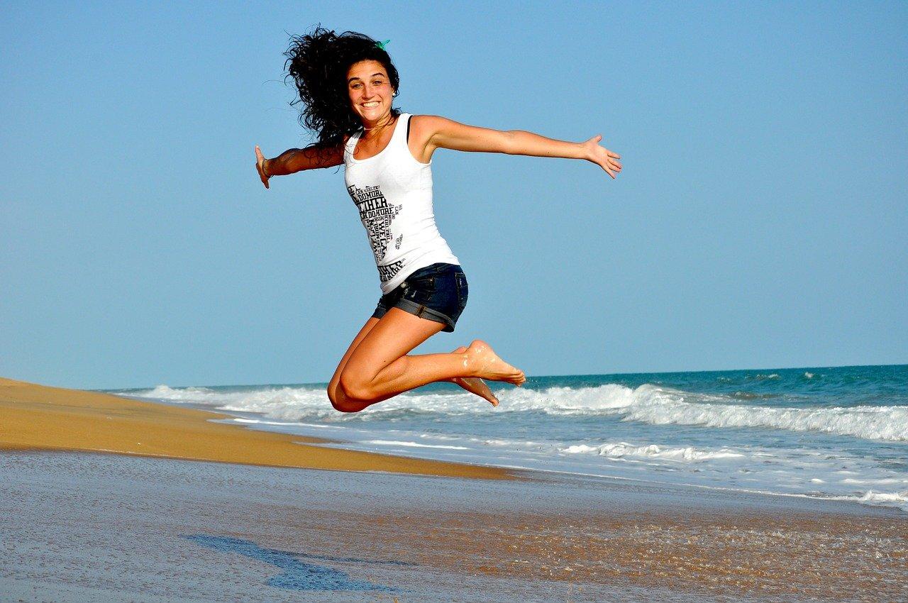 Mulher feliz na praia mesmo longe do ex namorado
