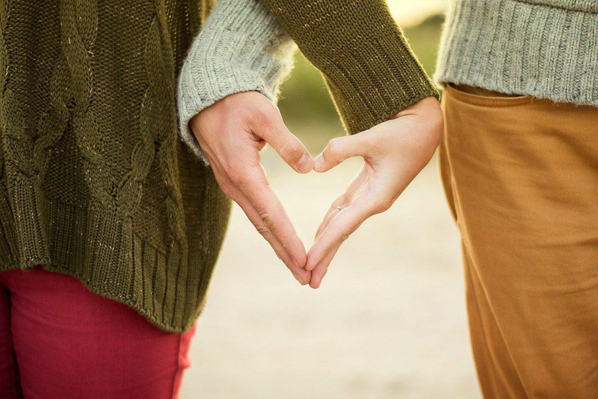 Casal que namora à distância fazendo sinal de coração